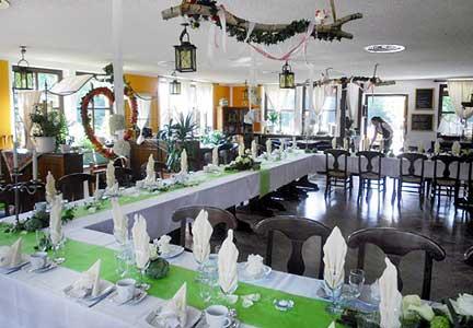 Festlich eingedeckte Tische im festlich geschmückten Saal